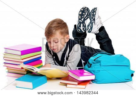 Cute teenager boy with backpack and books. Smiling schoolboy isolated on white background. Full height portrait happy child lying on floor. Back to school.