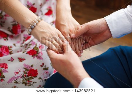 Husband holding hands of his young pregnant wife, closeup