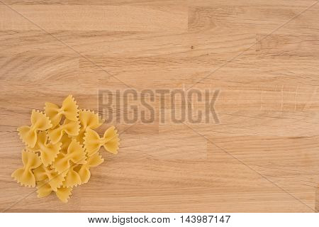 Dried italian bowtie pasta or farfalle over wooden background