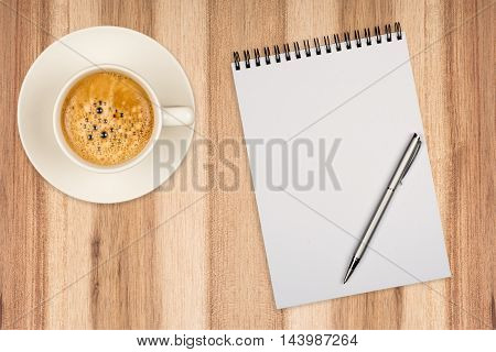 Coffee cup spiral notebook and pen on the wooden table