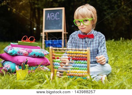 little boy with glasses for counting abacus. Back to school concept.