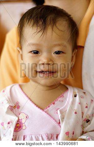 Cute Asian infant baby in pink dress is sitting and smiling near her mom