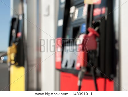Blurred image of gas pumps on sunny day.
