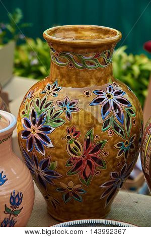 Colorful decorative jug decorated with flowers - handmade pottery clay glazed in natural sunlight against a background of other ceramic products