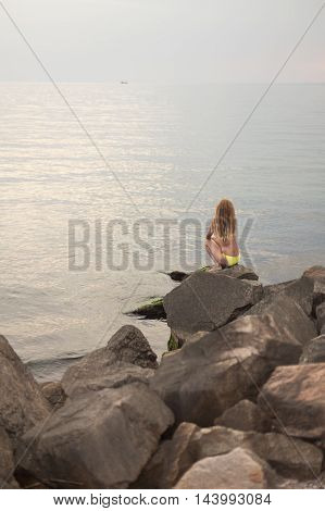 Lonely woman in a swimsuit sitting on the rocks by the sea at looking to the into the distance
