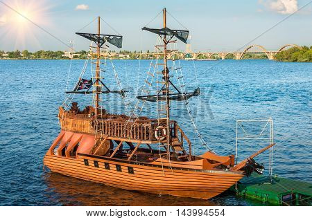 the pirate ship came into the port on the background the city bridge in good weather