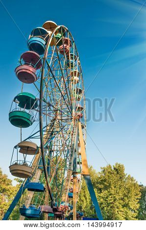 multi-colored Ferris wheel against the blue sky and green trees on a summer day