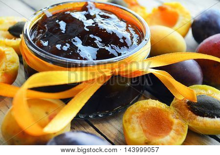 apricot and plum jam and fresh fruit on the wooden table