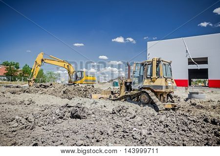 View on construction site with machinery bulldozer is leveling construction site. Landscape transform into large urban area.