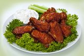 stock photo of chicken wings  - Platter of buffalo wings with a blue cheese dipping sauce and celery sticks - JPG