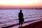 picture of unawares  - Silhouette of a man walking down the beach and stopping to stare - JPG
