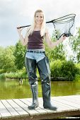image of fisherwomen  - fishing woman with landing net standing on pier - JPG