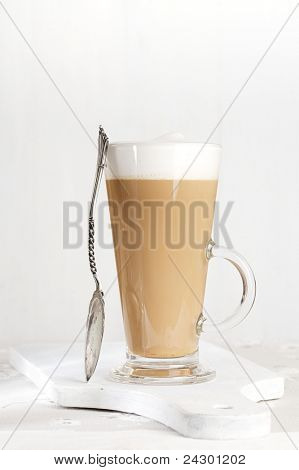coffee latte with frothy milk in tall glass, rustic style, white wood