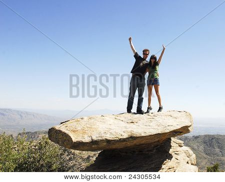 A young couple standing on a precarious rock formation