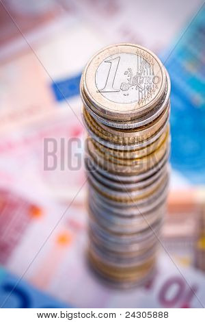 Big stack of euro coins with euro notes.