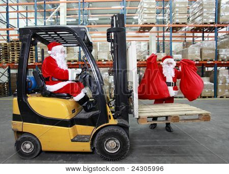 Two santa clauses as a workers in modern storehouse full of goods. One on forklift, another is lifting sacks full of presents.