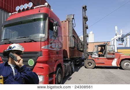 trucks waiting for cargo containers in busy commercial port