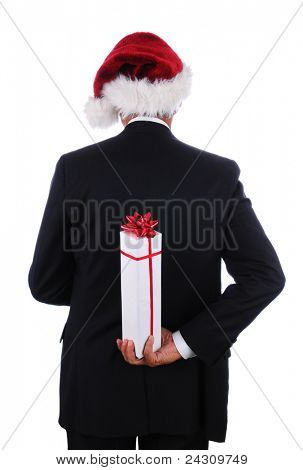 Businessman wearing a Santa Hat holding a Christmas present behind his back on a white background