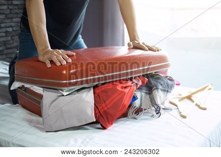 poster of Travel And Vacation Concept, Happiness Young Man Packing A Lot Of His Clothes And Stuff Into Suitcas