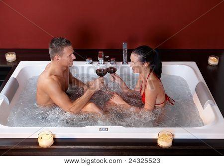¿Pareja celebrando en jacuzzi, vidrios de vino que tintinea, sonriendo.?