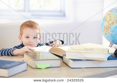 Little child prodigy learning at home, sitting at table, smiling.?