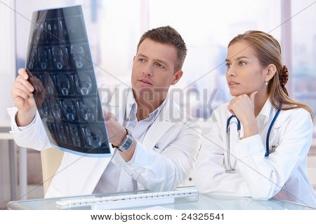 Two doctors studying x-ray image, consulting in bright office.?