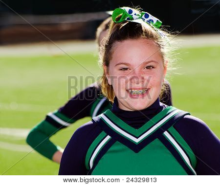Portrait of adolescent girl cheerleader at youth American football game.
