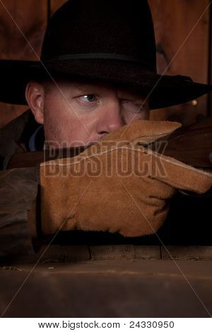 Cowboy Looking Down A Gun