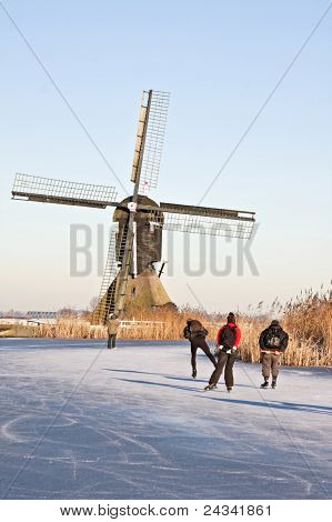 Typically dutch: ice skating on a frozen canal with view on a windmill on a cold winterday in the Ne