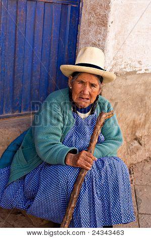 Peruvian Woman Sits On A Step At A Market, Pisac, Peru