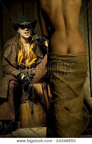 Cowboy looking at naced bondwoman against wooden background