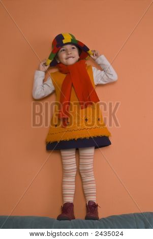 Litle Girl In Orange Dress Playing With Bonnet