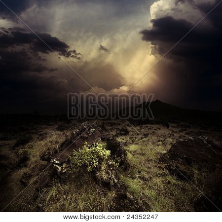 Storm dark clouds over volcanic valley with grass and rocks. Mountain Agung in Bali. Indonesia