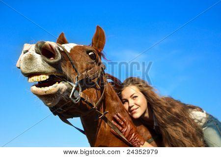 Menina bonita, cavalgando um cavalo com um senso de humor. Foco é o cavalo de focinho