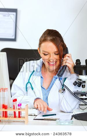 Smiling Female Medical Doctor Talking On Phone And Looking In Clipboard