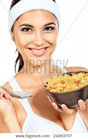 Portrait of a beautiful young woman eating cereal. Isolated over white background.