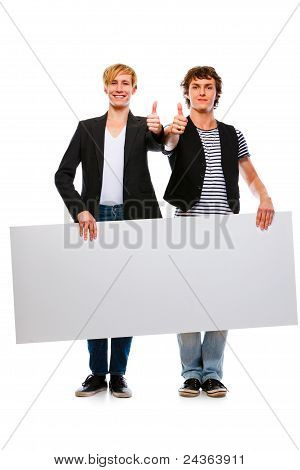 Two Cheerful Young Men Holding Blank Billboard And Showing Thumbs Up