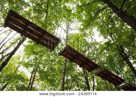 Dangerous ropeway with tether in rope park, trees with green leaves and sky