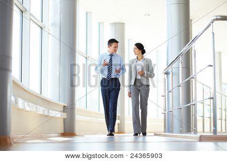 Zuversichtlich Geschäftspartner zu Fuß nach unten im Büro Gebäude und sprechen