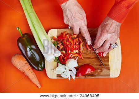 Senior Woman's Hands Cutting Vegetables