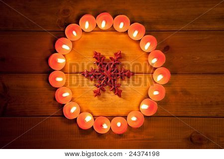 christmas candles circle over wood and red snowflake symbol
