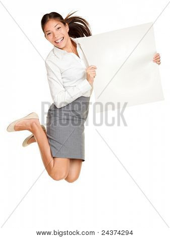 Showing sign. Woman jumping holding poster of paper, blank and empty with copy space. Casual business woman jumping excited smiling happy and cheerful isolated on white background.