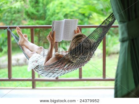 Young woman lying in a hammock in a garden and reading a book
