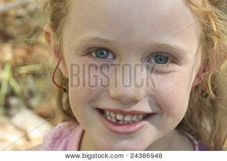 A Little Red Haired Girl With Blue Eyes