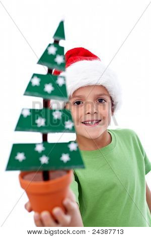 Happy kid in santa hat holding christmas decoration fir tree - closeup, isolated