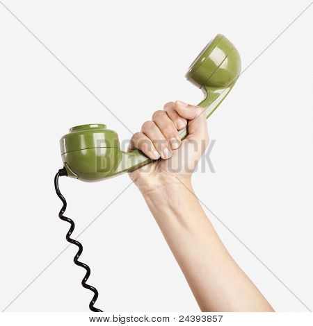 Female hand holding a green handpiece from a vintage telephone