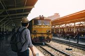 Young Asian Man Traveler With Backpack And Hat Standing And Holding Map Waiting Train For Travel At  poster