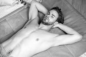 Macho With Bare Torso, Chest Lie On Blue Bed Cover. Comfort, Rest, Relax. Desire, Erotic Concept poster
