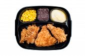 stock photo of frozen tv dinner  - A cooked tv dinner of fried chicken corn mashed potatoes and dessert in a plastic black tray - JPG