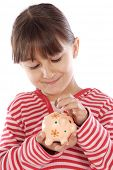 stock photo of thrift store  - adorable girl putting its savings in your money box - JPG
